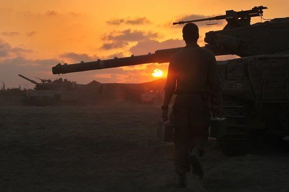 Een Israëlische soldaat loopt langs een tank bij de grens van Israël met de Gazastrook.