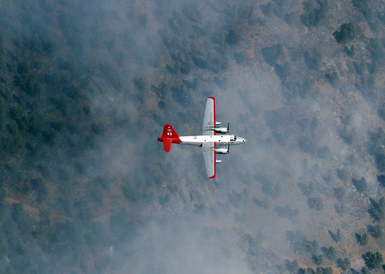 In this aerial photograph, a slurry bomber passes through clouds of smoke on the way to making a drop on a ridge as the Lower North Fork Wildfire burns near the foothills community of Conifer, Colo., southwest of Denver on Tuesday, March 27, 2012. Firefighters are now able to actively battle the blaze on the ground that started on Monday and has already destroyed at least 16 homes in the rugged terrain. (AP Photo/David Zalubowski)