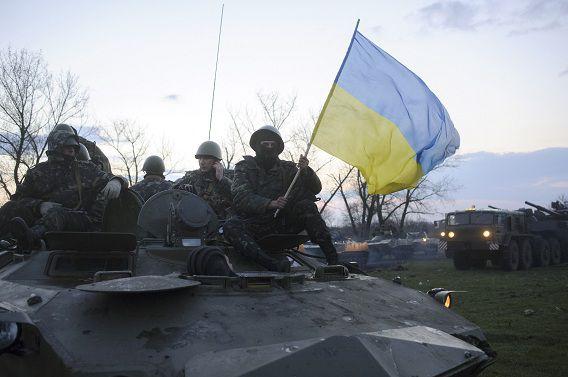 Oekraïense soldaten op een tanker met de nationale vlag, ongeveer 70 kilometer van de oostelijke stad Slavjansk, waar een overheidsgebouw is bezet door pro-Russische aanhangers.