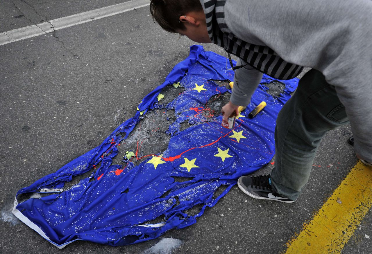 A student pours red paint on an EU flag in front of the Greek Parliament in Athens on March 21, 2011 during a demonstration organized by the Communist-affiliated university and high-school student union against the Western-led forces military operations in Libya. Demonstrators, carrying banners with slogans in solidarity with the people of Libya, demanded no participation and no involvement by Greece in the operations. AFP PHOTO / LOUISA GOULIAMAKI