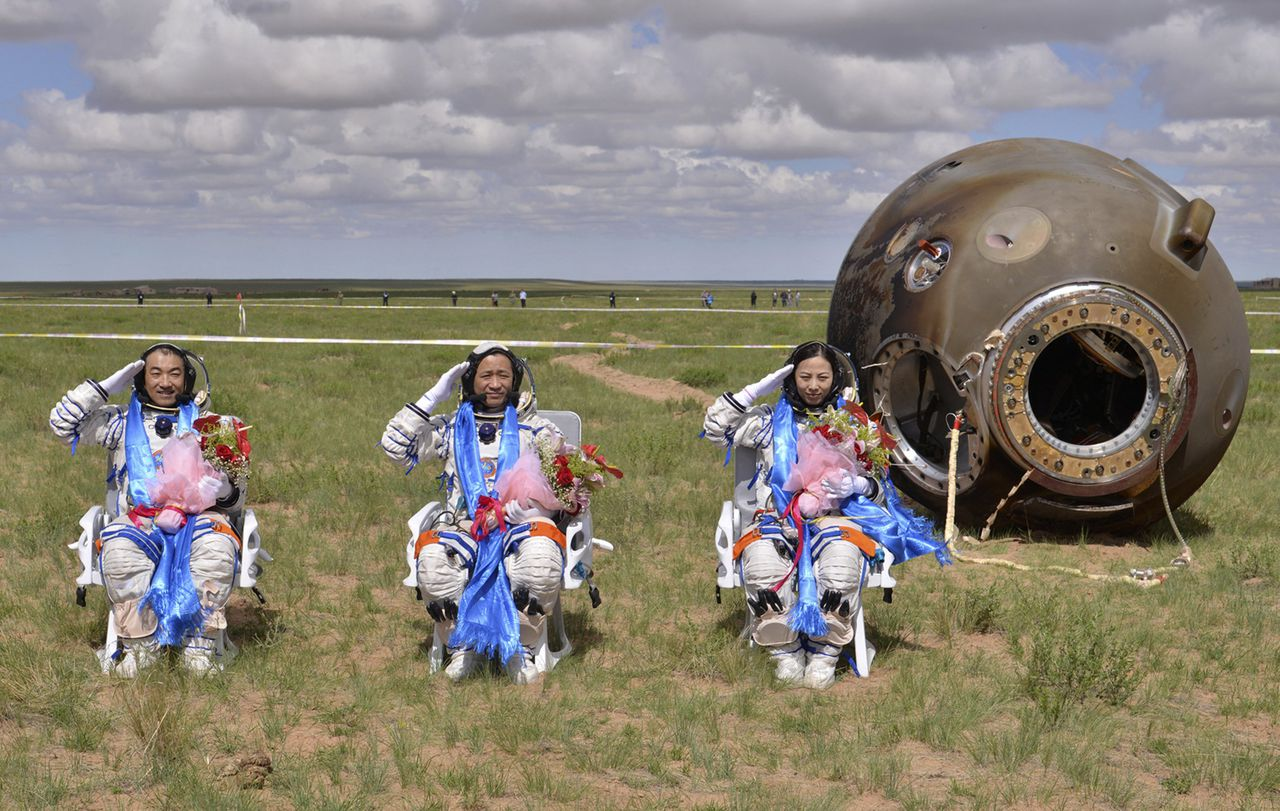 Astronauts (L-R) Zhang Xiaoguang, Nie Haisheng and Wang Yaping salute after returning to earth in the re-entry capsule of China's Shenzhou-10 spacecraft at its main landing site in north China's Inner Mongolia Autonomous Region, June 26, 2013. Three Chinese astronauts returned to Earth on Wednesday, touching down in north China's Inner Mongolia after a successful 15-day mission in which they docked with a manned space laboratory. REUTERS/Stringer (CHINA - Tags: SCIENCE TECHNOLOGY TPX IMAGES OF THE DAY) CHINA OUT. NO COMMERCIAL OR EDITORIAL SALES IN CHINA