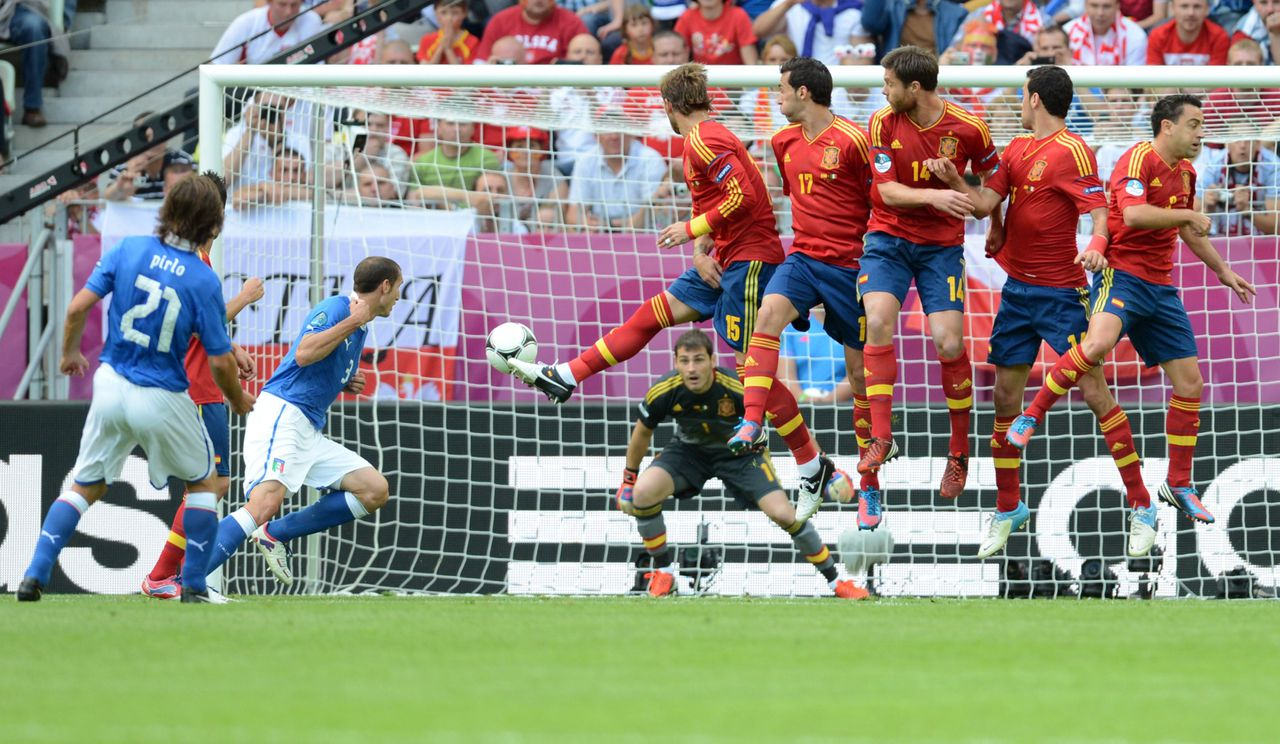 Italian midfielder Andrea Pirlo (L) shoots a free kick as Spanish goalkeeper Iker Casillas eyes the ball during the Euro 2012 championships football match Spain vs Italy on June 10, 2012 at the Gdansk Arena. AFP PHOTO / CHRISTOF STACHE