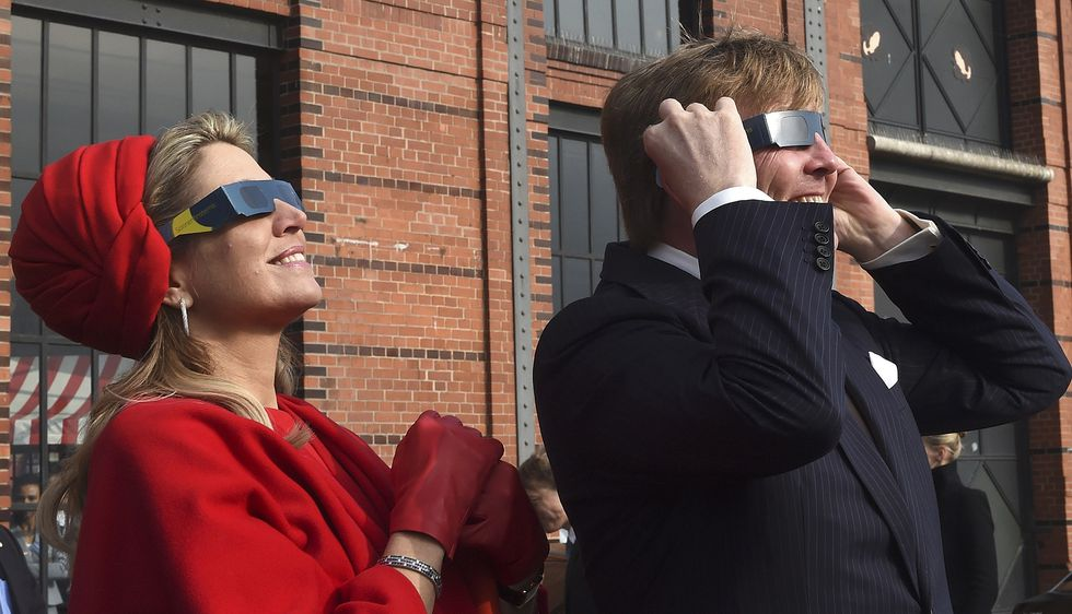 Dutch King Willem-Alexander and Queen Maxima wear sunglasses as they watch a partial solar eclipse in Hamburg