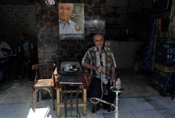 Een man rookt een waterpijp onder een poster van de Egyptische presidentskandidaat Ahmed Shafiq tijdens de tweede dag van de presidentsverkiezingen.