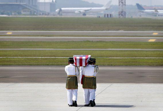 Een kist met het stoffelijk overschot van een van de slachtoffers wordt tijdens de ceremonie gedragen door soldaten.