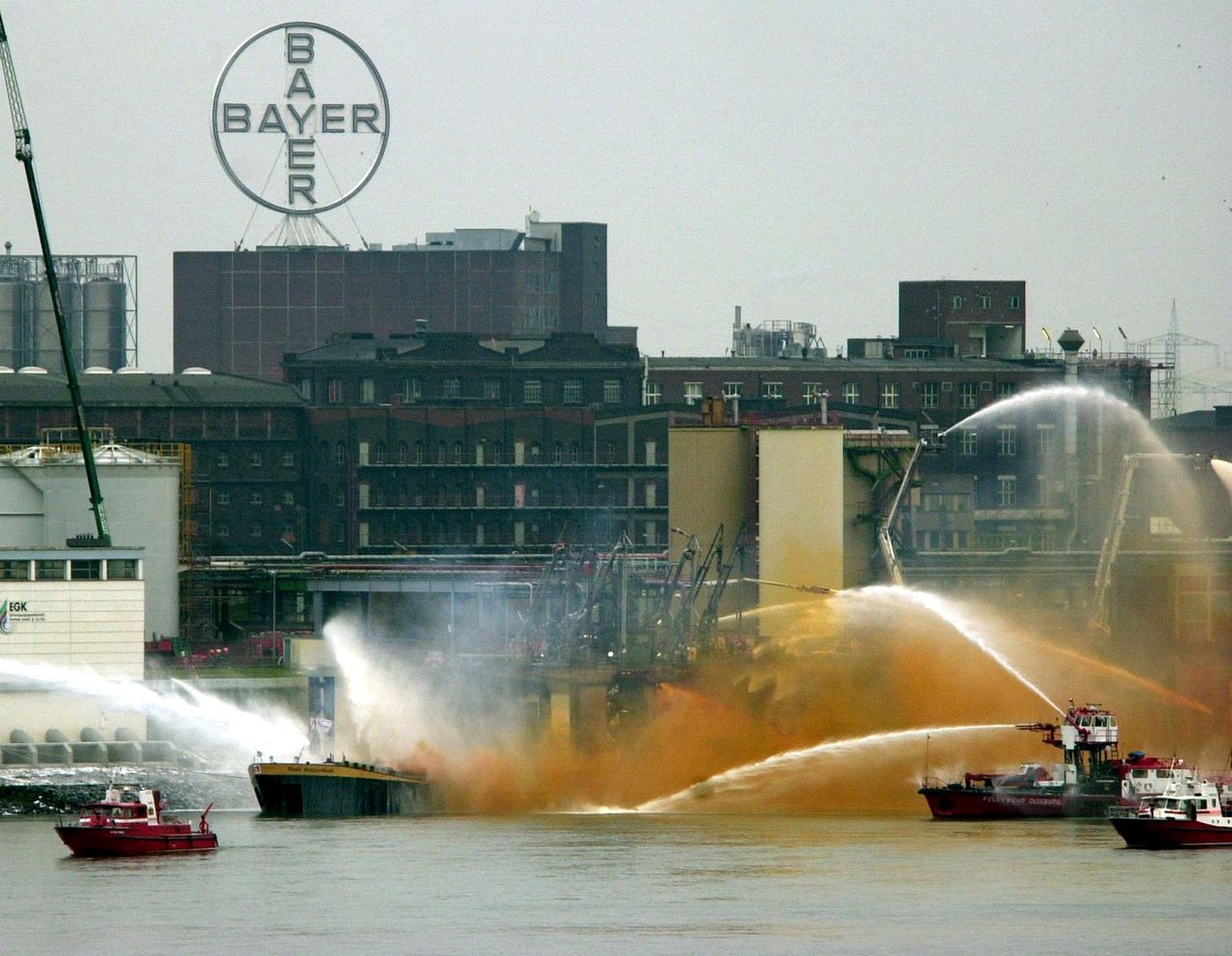 Firemen struggle to prevent a burning chemical tanker ship from leaking its entire 1,800 tonnes load of highly corrosive nitric acid into the Rhine at Krefeld 21 November 2001. A quantity of nitric acid has already escaped in the form of fumes from the Netherlands-registered Stolt Rotterdam, which began leaking and caught fire at the Bayer chemical company's wharf.