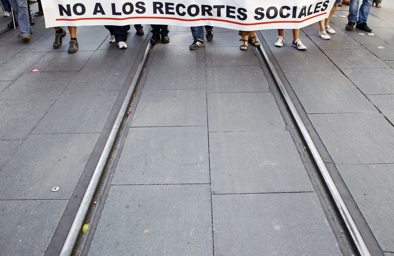 """Workers and union members hold a banner as they march during a demonstration in the Andalusian capital of Seville October 1, 2011, to demand for decent employment rights in the civil service. The banner reads: """"No social cuts"""". REUTERS/Marcelo del Pozo (SPAIN - Tags: BUSINESS EMPLOYMENT CIVIL UNREST)"""
