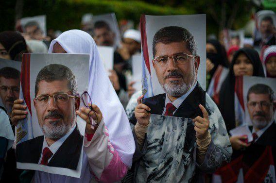 Maleisische islamisten houden posters omhoog met de afbeelding van Morsi