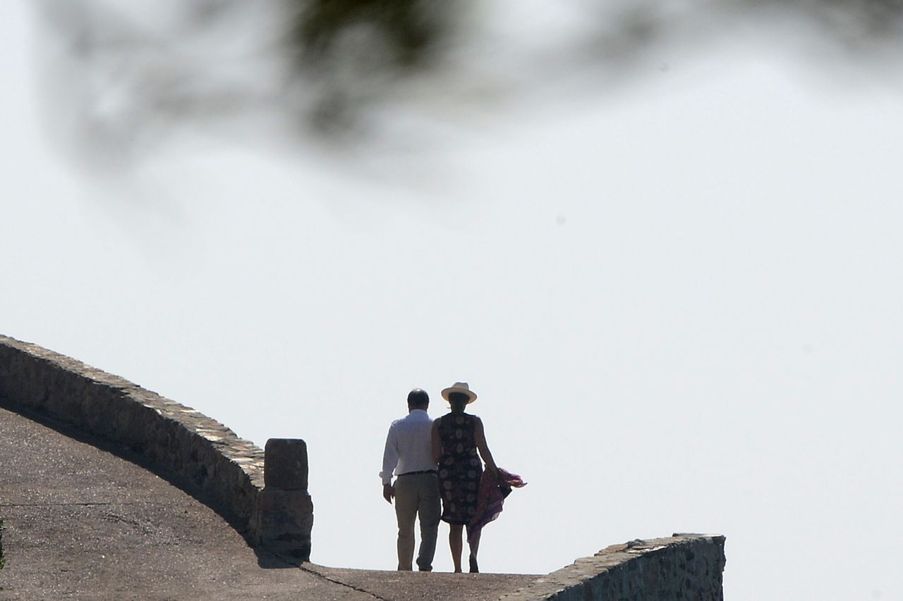 French President François Hollande (L) and his partner Valerie Trierweiler go to the beach at the Fort de Bregancon in Bormes-les-Mimosas, southeastern France, on August 3, 2012. François Hollande and Valerie Trierweiler spend their holidays at the Bregancon Fort, one of the official presidential holiday residences since 1968. TOPSHOTS/AFP PHOTO / BORIS HORVAT