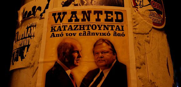 """Caption: A poster depicting Greek Prime Minister George Papandreou (L) and Finance Minister Evangelos Venizelos in seen on a light pole in Athens' Syntagma square November 4, 2011 the words read """"Wanted by the Greek people"""". Greek parliamentarians prepared to give their verdict on Papandreou on Friday in a confidence vote which could decide the fate of both the nation's European bailout deal and the global economy. REUTERS/Panayiotis Tzamaros (GREECE - Tags: POLITICS BUSINESS)"""