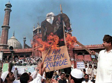 """(FILES) In this file picture taken on 19 February 1999 Indian Muslims burn an effigy of Indian-born British author Salman Rushdie, the author of the novel """"The Satanic Verses"""", as they shout anti-government slogans during a demonstration near India's largest mosque in New Delhi. Rushdie, whose novel angered Muslims around the world more than ten years ago, withdrew on 20 January 2012 from India's largest literary festival, saying he feared assassination after his participation was opposed by hardline Muslim groups. AFP PHOTO/FILES/RAVEENDRAN"""