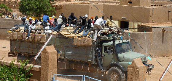 Caption: West African migrants return from Libya to Niger on a truck, in Agadez, on September 7, 2011. For many Touaregs and West African migrants in Niger, the fall of Mouammar Kadhafi from power has meant the loss of an important ally who had until now maintained strong relations with the community throughout Mali, Niger, Algeria, and Burkina Faso. AFP PHOTO / BOUREIMA HAMA