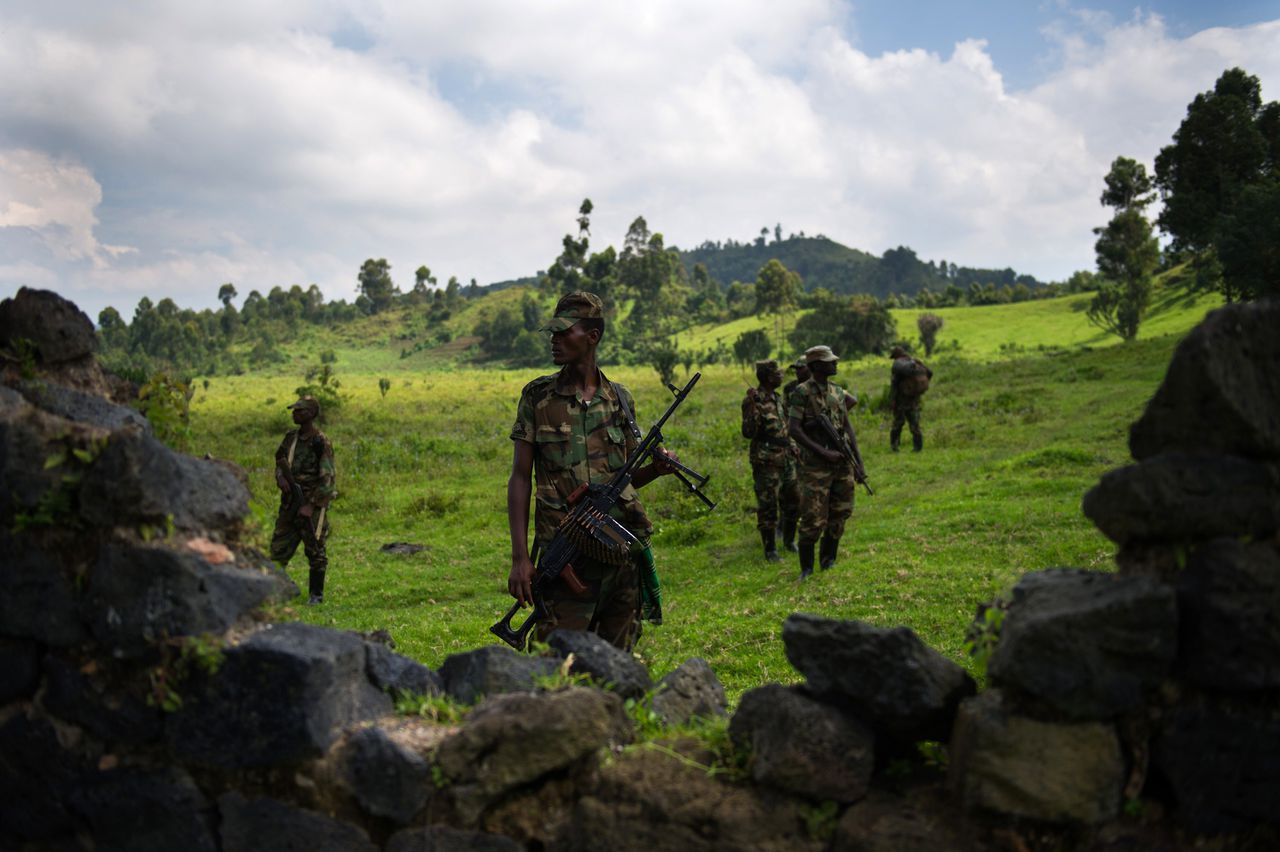 """M23 rebels stand at a small base in the hills of Kanyarucinya on the outskirts of Goma, in the east of the Democratic Republic of the Congo, on November 19, 2012. DR Congo's M23 rebels who have closed in on the main eastern city of Goma warned that they will continue their fight against the government unless it opens direct talks with them within 24 hours. The rebels said in a statement they will """"pursue the resistance against the government of Kinshasa until it falls"""" unless it starts """"direct political negotiations"""" with the insurgents within the next 24 hours and demilitarises Goma and the city's airport. AFP PHOTO/PHIL MOORE"""
