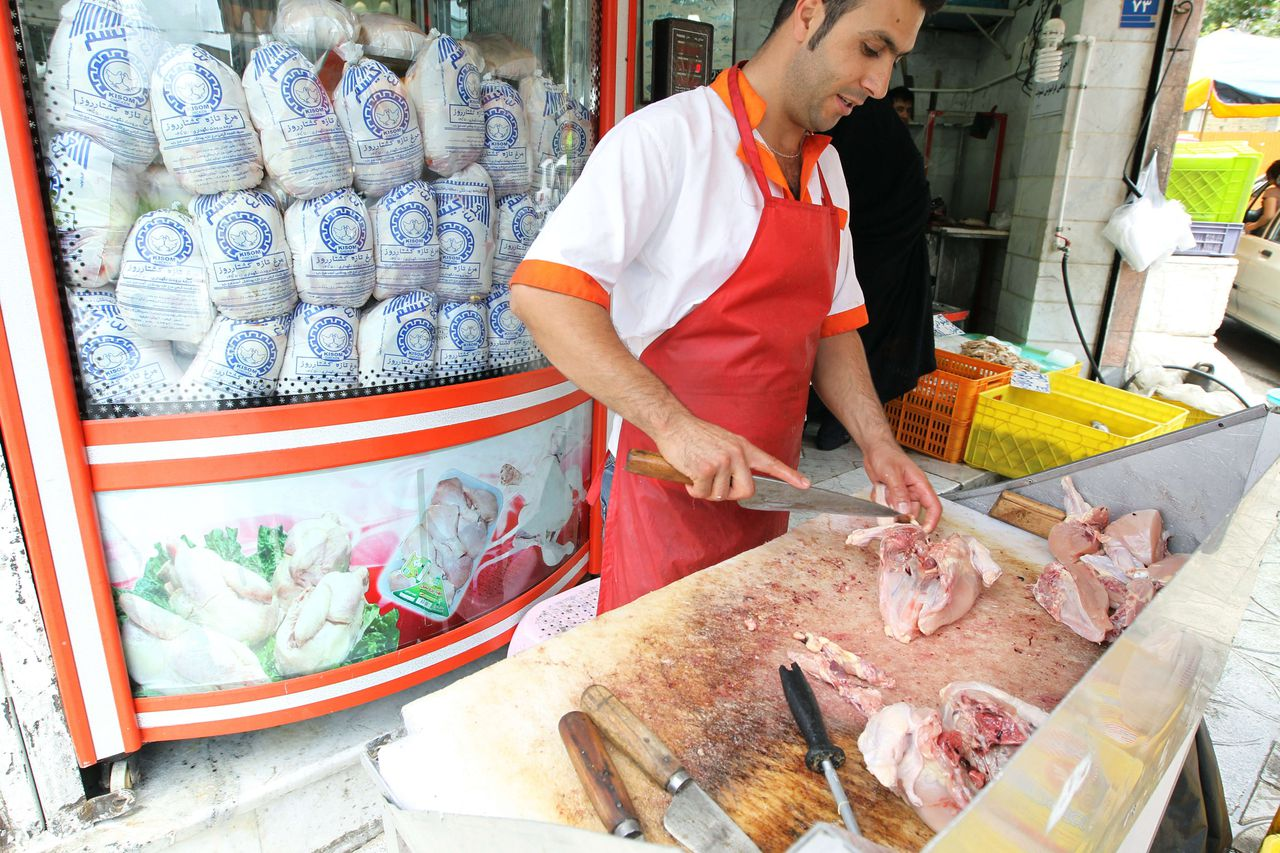 TO GO WITH AFP STORY OF SIAVOSH GHAZI An Iranian butcher cuts a chicken on July 24, 2012 outside his shop in Tehran as top government officials and lawmakers in the Islamic republic agreed in a meeting to budget cuts in a bid to shore up an economy struggling with Western sanctions and inflation, media reported. The United States and the European Union this month severely ramped up their sanctions on Iran with the aim of strangling its oil-export dependent economy in a bid to force it to roll back its nuclear activities. AFP PHOTO/ATTA KENARE