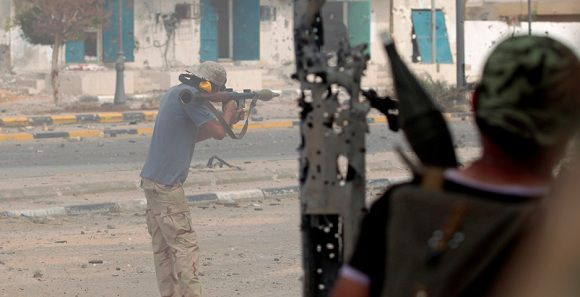 Caption: An anti-Gaddafi fighter fires a rocket propelled grenade (RPG) during clashes with Gaddafi forces at the front line in the center of Sirte October 16, 2011. REUTERS/Thaier al-Sudani (LIBYA - Tags: CONFLICT CIVIL UNREST)