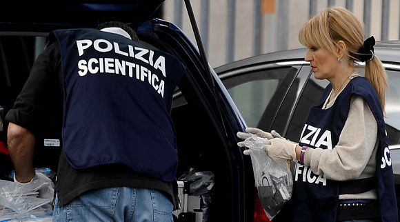 Caption: Italian scientific police collect evidence inside the parking lot of the Equitalia building, a public company responsible for collecting taxes in Italy, after a letterbomb exploded in its central office in Rome on December 9, 2011. The head of Italy's tax collection agency was wounded to the hand and face by a letter bomb on Friday, two days after Italian anarchists claimed responsibility for a bomb sent to the head of Deutsche Bank. AFP PHOTO / FILIPPO MONTEFORTE
