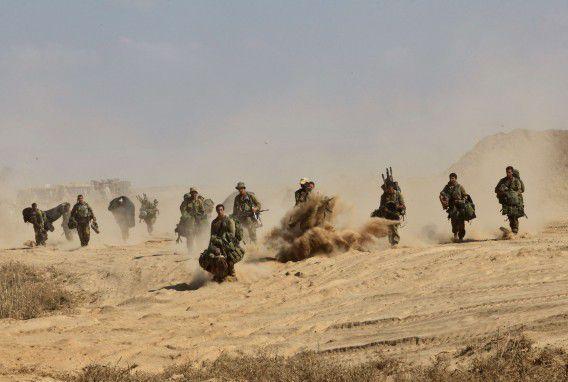 Israëlische soldaten lopen bij de grens van Israël met de Gazastrook.