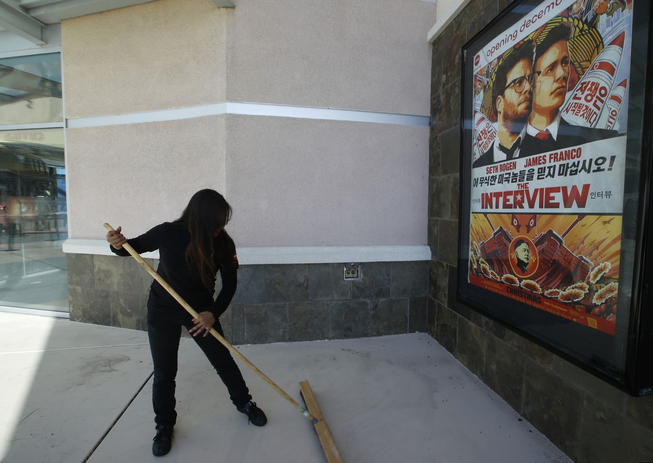 """A movie theater worker sweeps rain water under a poster for the movie """"The Interview"""" at the AMC Glendora 12 movie theater, Wednesday, Dec. 17, 2014, in Glendora, Calif. The fallout from the Sony Pictures Entertainment hack that began four weeks ago exploded Tuesday after the shadowy group calling themselves Guardians of Peace escalated their attack beyond corporate espionage and threatened moviegoers with violence reminiscent of the terrorist attacks of September 11, 2001. (AP Photo/Damian Dovarganes)"""
