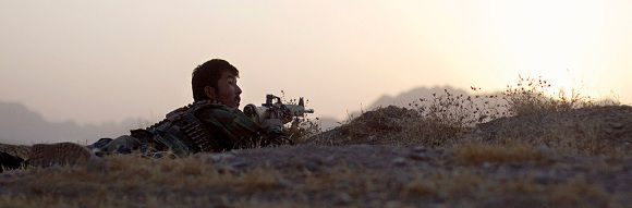 Caption: In this July 21, 2011 photo, an Afghan National Army soldier at left takes cover as shots come in from a second direction during a fire fight with insurgents in the village of Salaam Bazaar in Helmand province, Afghanistan. (AP Photo/David Goldman)