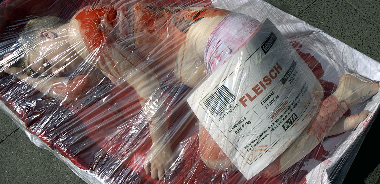An activist of animal rights organisation PETA is smeared with blood under cellophane during a protest action in Berlin, Germany, 20 May 2008. Under the motto 'Put yourself in the place of animals', PETA suggests how human meat sold in a supermarket might look like and protests on consumption of meat. Photo: KLAUS-DIETMAR GABBERT