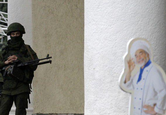 Een gewapende man in militair uniform patrouilleert voor het vliegveld van Simferopol, de hoofdstad van de Krim.