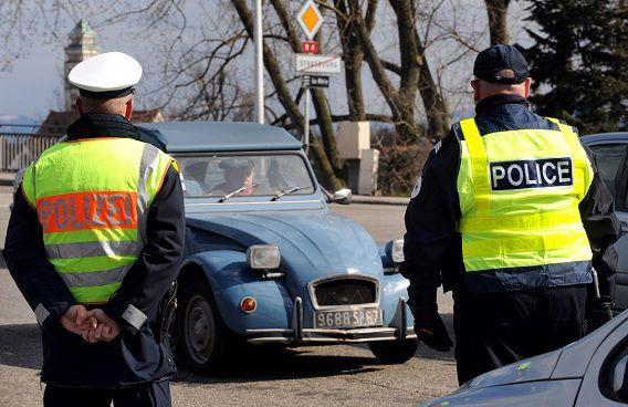 Een Duitse en Franse agent controleren de Europa-brug in Straatsburg.