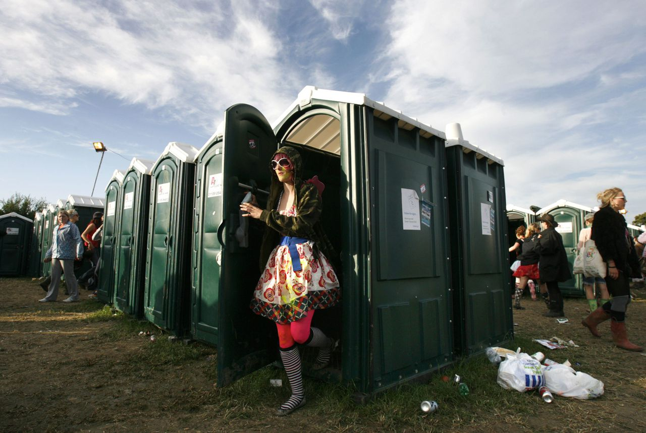 A festival-goer leaves the toilets at the Glastonbury Festival 2008 in Somerset in south west England June 29, 2008. REUTERS/Luke MacGregor (BRITAIN)