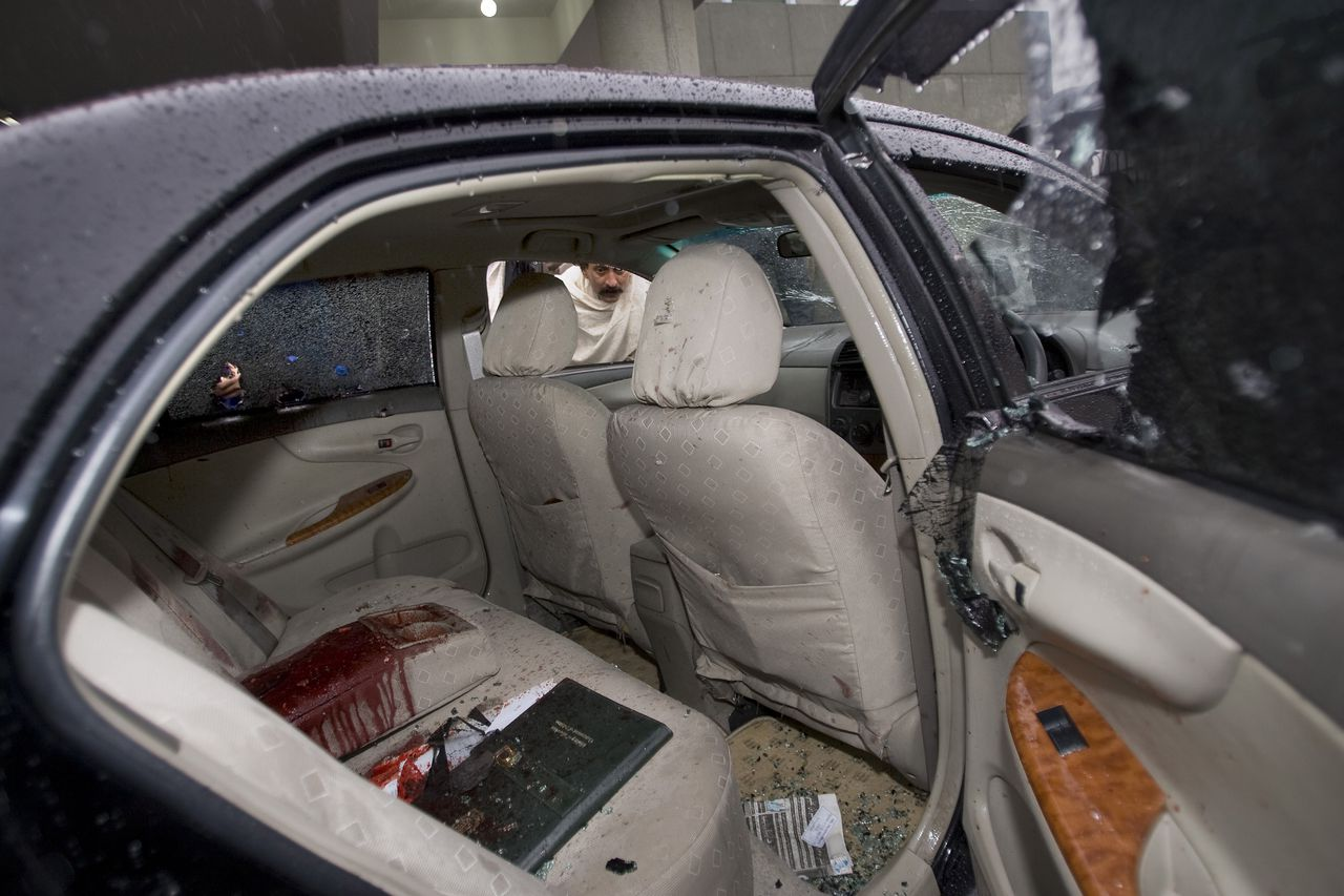A Pakistani looks into the blood-stained damaged car of slain Pakistan's government minister for religious minorities Shahbaz Bhatti, outside emergency the ward of a local hospital in Islamabad, Pakistan, Wednesday, March 2, 2011. Gunmen shot and killed the Christian Pakistani government minister for religious minorities on Wednesday, the latest attack on a high-profile figure threatened by Muslim militants for urging reform of harsh blasphemy laws that impose the death penalty for insulting Islam. (AP Photo/Anjum Naveed)