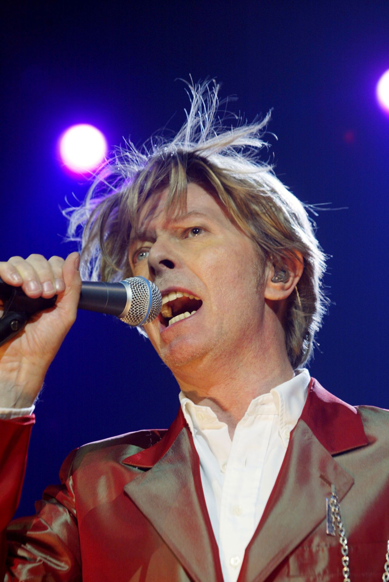"(FILES) In this file picture taken on September 24, 2002 British singer David Bowie performs during a concert at the Zenith in Paris. British rock icon David Bowie broke a decade-long musical silence on January 8, 2013, unveiling a new single to coincide with his 66th birthday and announcing that he will release an album in March. The outlandish star surprised fans by posting a video for the single, entitled ""Where are We Now?"", on his website, and it will also be available to download on iTunes. AFP PHOTO MARTIN BUREAU"