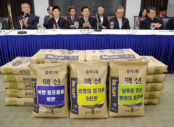 Some 30 leaders of South Korean religious and civic groups hold a press conference urging the government to approve a plan to send 5,000 tonnes of flour to North Korea, as sacks of flour are piled up in Seoul on May 23, 2011. Civic and religious leaders urged South Korea's government to resume food aid for North Korea and to soften its stance towards the impoverished communist neighbour. AFP PHOTO/JUNG YEON-JE