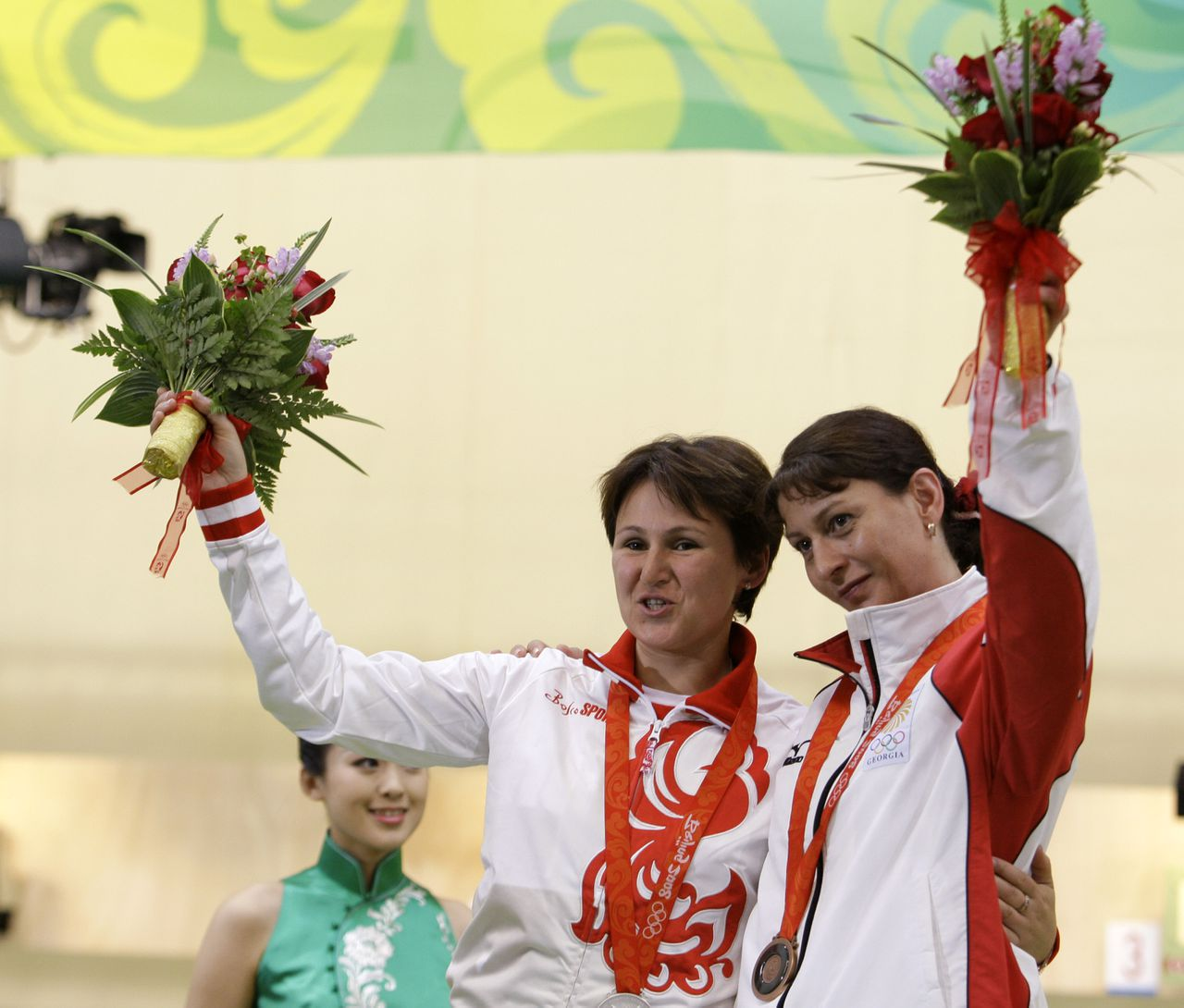 Russia's Natalia Paderina, left, and Georgia's Nino Salukvadze hug and wave during the medal ceremony after the women's 10 meter air pistol final at the Beijing 2008 Olympics in Beijing, Sunday, Aug. 10, 2008. Paderina won the silver medal and Salukvadze won bronze. (AP Photo/Sergey Ponomarev)