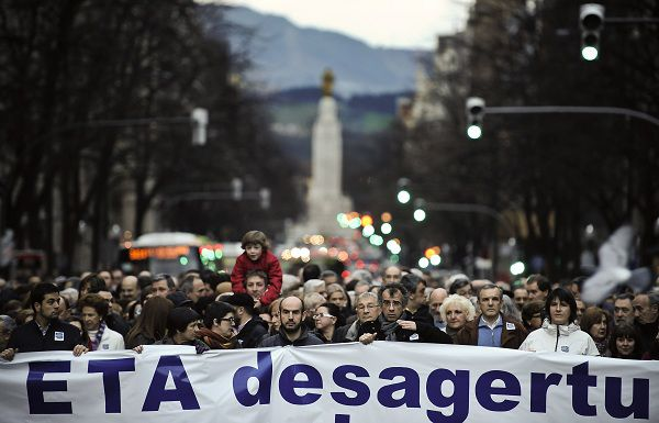 Basque citizens hold up a banner reading: ''ETA, Disarmament'' during a rally for the peace in Bilbao northern Spain, Saturday Jan. 29, 2011. After 50 years of violence, the Basque citizens movement, ''Gesto por La Paz'' has called for a total cease-fire of the Basque armed separatist group ETA. (AP Photo/Alvaro Barrientos)