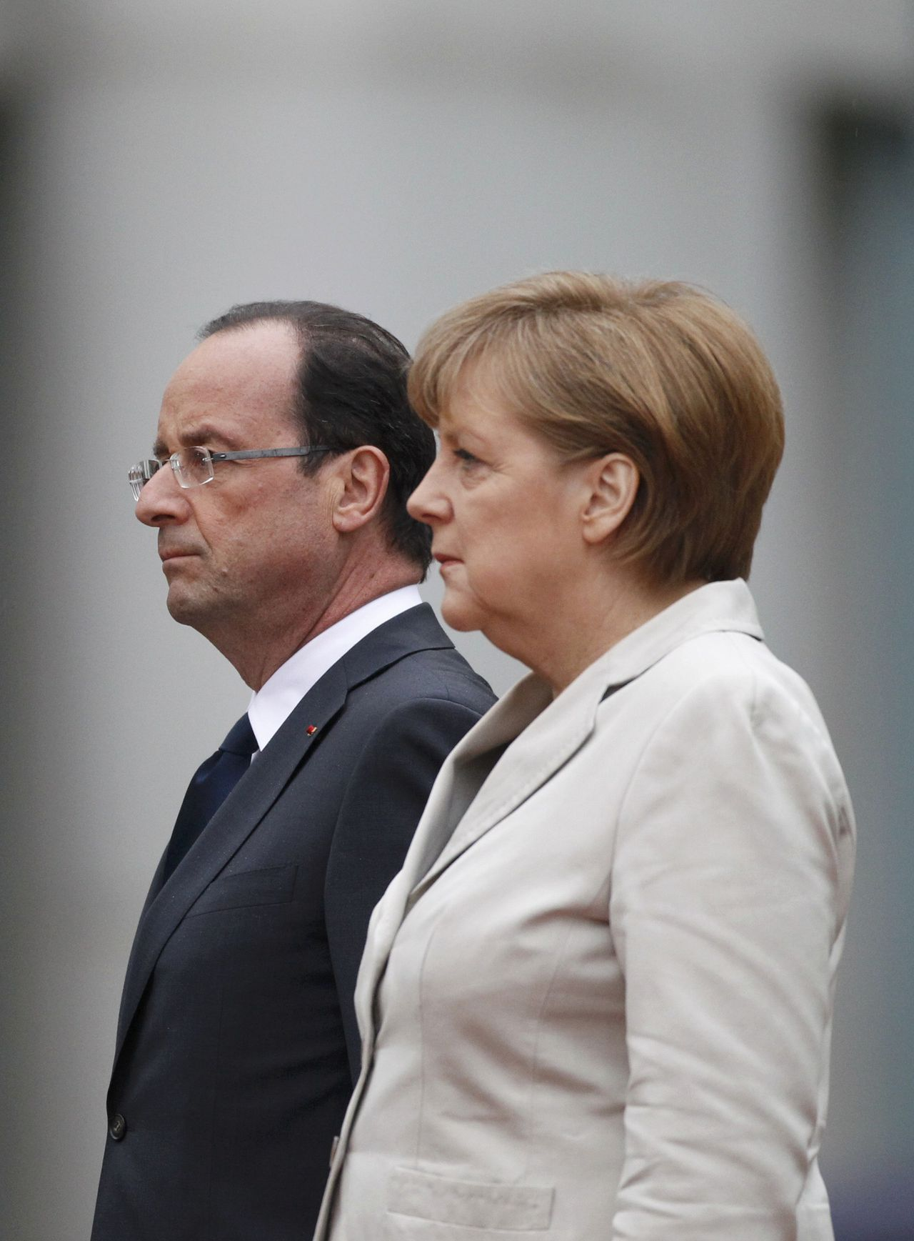 German Chancellor Angela Merkel and French President Francois Hollande listen to national anthems during a ceremony at the Chancellery in Berlin, May 15, 2012. Hollande called for a European pact for growth to balance out German-driven austerity measures in his inaugural address on Tuesday, hours before taking his challenge to Chancellor Angela Merkel in Berlin. Sworn in with all the pomp of the French Republic, Hollande won support from Germany's opposition Social Democrats (SPD), who vowed to use their parliamentary blocking power to delay ratifying a European budget discipline treaty until Merkel accepts accompanying measures to boost growth and jobs. REUTERS/Thomas Peter (GERMANY - Tags: POLITICS TPX IMAGES OF THE DAY)
