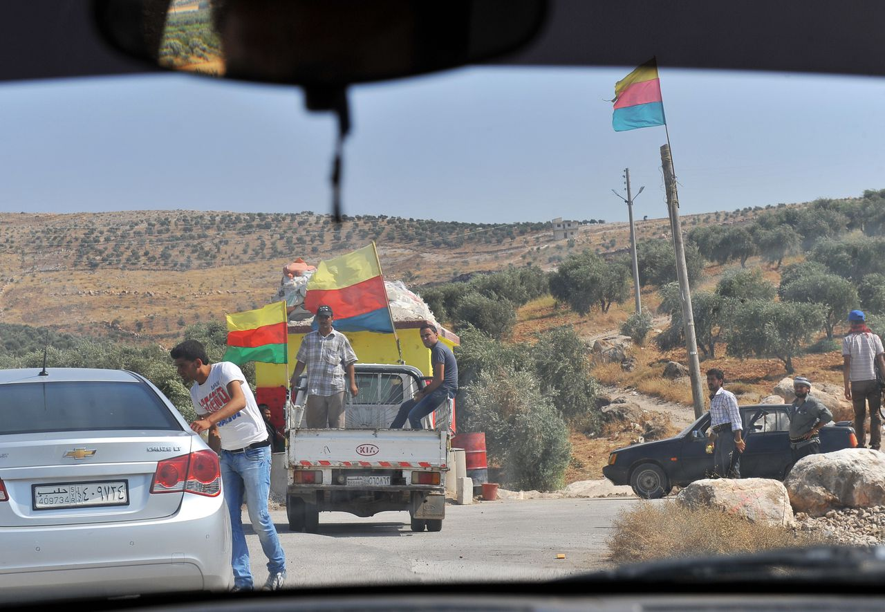 """Syrian Kurds guard a check point at the entrance of the Kurdish town of Jinderes, near the northern Syrian city of Aleppo, on July 22, 2012, as Kurdish activists on the Syria-Turkey border started taking control of towns in the area without encountering much resistance from the forces loyal to Syrian President Bashar al-Assad. Turkey said on July 29, it would do everything it could to prevent """"terrorist"""" formations near its border with Syria that would threaten its national security. AFP PHOTO / BULENT KILIC"""