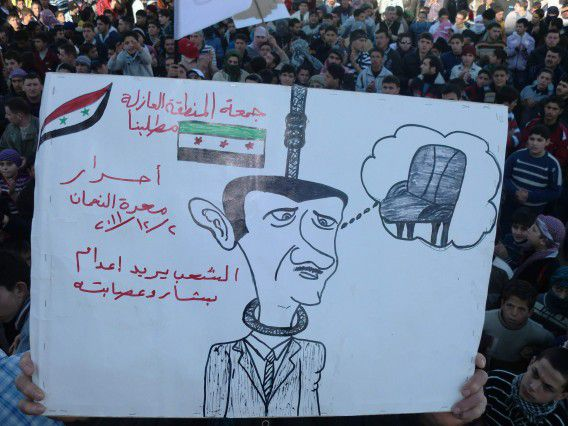 """A demonstrator protesting against Syria's President Bashar al-Assad holds a sign during a march through the streets after Friday prayers in Marat al Numan near Adlb December 2, 2011. The banner reads, """"People want the execution of Bashar and his gang"""". Picture taken December 2, 2011. REUTERS/Handout (SYRIA - Tags: POLITICS CIVIL UNREST) THIS IMAGE HAS BEEN SUPPLIED BY A THIRD PARTY. IT IS DISTRIBUTED, EXACTLY AS RECEIVED BY REUTERS, AS A SERVICE TO CLIENTS"""