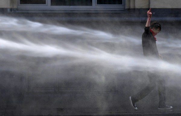 A demonstrator gestures in front of riot police as he is sprayed by water canons during a protest by European workers and trade union representatives to demand better job protection in the European Union countries in Brussels March 24, 2011. Tens of thousands of people marched through Brussels on Thursday to urge European leaders holding a two-day summit in the Belgian capital to scrap or ease austerity measures, which unions say will slow economic recovery and punish the poor. REUTERS/Eric Vidal (BELGIUM - Tags: POLITICS CIVIL UNREST BUSINESS)
