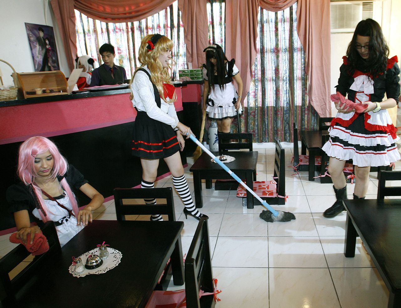 Cafe attendants, dressed up in maid uniforms, clean up at the MeiDolls Cafe in Cainta Rizal, east of Manila January 30, 2011. Philippines opened its first costume play (cosplay) maid cafe in the country where servers entertain customers with Japanese role playing culture. REUTERS/Cheryl Ravelo (PHILIPPINES - Tags: SOCIETY)