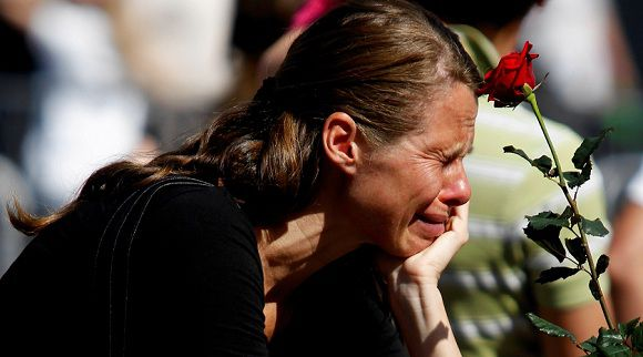 Caption: A woman cries as she pays her respects for the victims of attacks outside the Oslo cathedral July 31, 2011. Norwegians united in mourning on Friday as the first funerals were held a week after anti-Islam extremist Anders Behring Breivik massacred 77 people in attacks that traumatised the nation. REUTERS/Stoyan Nenov (NORWAY - Tags: CIVIL UNREST CRIME LAW OBITUARY)