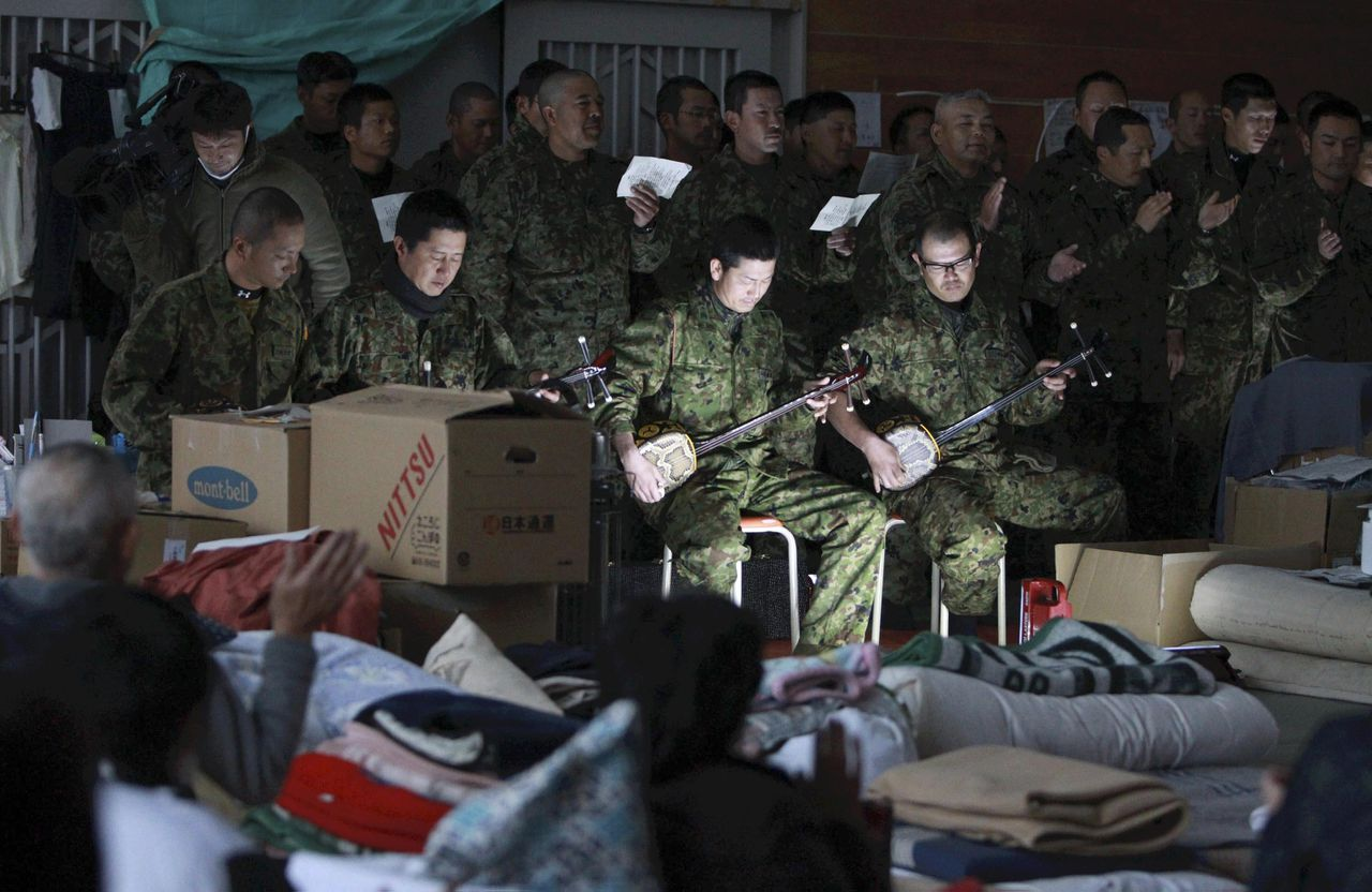 """Members of the Japan Ground Self-Defense Force's 15th Brigade play the Okinawan three-stringed instrument """"Sanshin"""" before evacuees at a shelter in the March 11 earthquake and tsunami devastated town of Minamisanriku, Miyagi Prefecture, northeastern Japan, Thursday, March 30, 2011. (AP Photo/Daisuke Uragami) JAPAN OUT, MANDATORY CREDIT"""