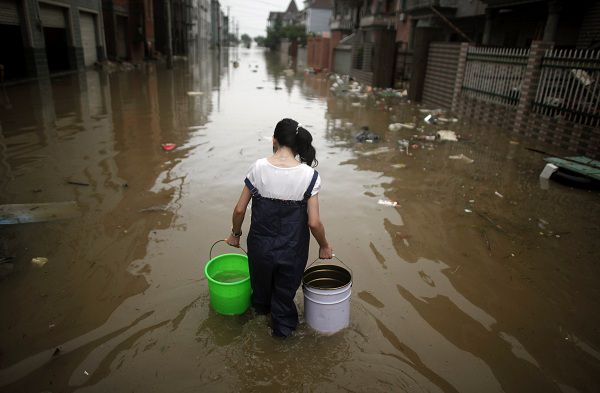 A girl carries two buckets of clean water to her house through a flooded area in Moshan village, Zhejiang province June 19, 2011. China has mobilised troops to help with flood relief and raised its disaster alert to the highest level after days of downpours forced the evacuation of more than half a million people in central and southern provinces. Central authorities have raised the disaster alert to the highest level 4, and the government is describing the floods in some areas, such as eastern Zhejiang province's Qianting River area, as the worst since 1955. REUTERS/Carlos Barria (CHINA - Tags: ENVIRONMENT DISASTER IMAGES OF THE DAY)