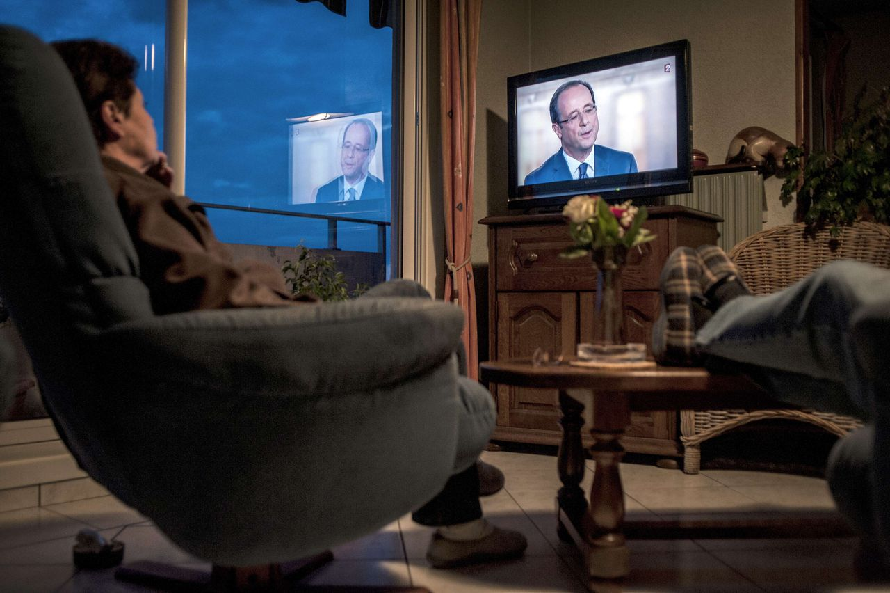 People watch on TV the televised national debate between the two candidates for the 2012 French presidential election, France's Socialist Party (PS)'s Francois Hollande and France's incumbent president and Union for a Popular Movement (UMP)'s Nicolas Sarkozy between the two rounds of the presidential election on May 2, 2012 at their home in Meyzieu, near Lyon, central eastern France. AFP PHOTO JEFF PACHOUD