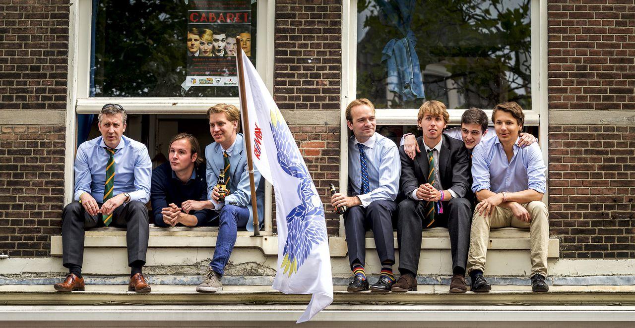 Leden en reünisten kijken naar de Maskerade-optocht door het centrum van Leiden ter ere van het 200-jarig bestaan van studentenvereniging Minerva.