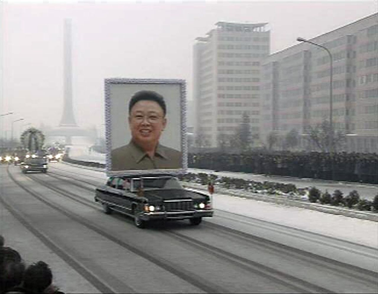 """A limousine carrying a portrait of late North Korean leader Kim Jong-il leads his funeral procession past crowds on a street in Pyongyang in this still image taken from video December 28, 2011. North Korea's military staged a huge funeral procession on Wednesday in the snowy streets of the capital Pyongyang for its deceased """"dear leader,"""" Kim Jong-il, readying a transition to his son, Kim Jong-un. REUTERS/KRT via Reuters TV (NORTH KOREA - Tags: POLITICS OBITUARY TPX IMAGES OF THE DAY) NORTH KOREA OUT. NO COMMERCIAL OR EDITORIAL SALES IN NORTH KOREA. NO SALES. NO ARCHIVES. FOR EDITORIAL USE ONLY. NOT FOR SALE FOR MARKETING OR ADVERTISING CAMPAIGNS. NORTH KOREA OUT. NO COMMERCIAL OR EDITORIAL SALES INNORTH KOREA"""