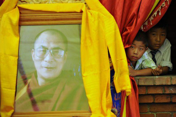 Exiled Tibetans look on past a portrait of the Dalai Lama (L) during an event celebrating the Tibetan spiritual leader's 76th birthday at the Namgyal School in Kathmandu on July 6, 2011. Riot police in the Nepalese capital Kathmandu on July 6 arrested three Tibetan exiles who were attempting to celebrate the birthday of their spiritual leader. Hundreds of exiles from Tibet, who have fled their highly militarised homeland, attempted to attend a birthday event for the Tibetan spiritual leader at a school on the outskirts of Kathmandu. Nepal has a long border with China and is home to around 20,000 exiled Tibetans, but the government has taken an increasingly hardline on their activities under pressure from Beijing. AFP PHOTO/Prakash MATHEMA