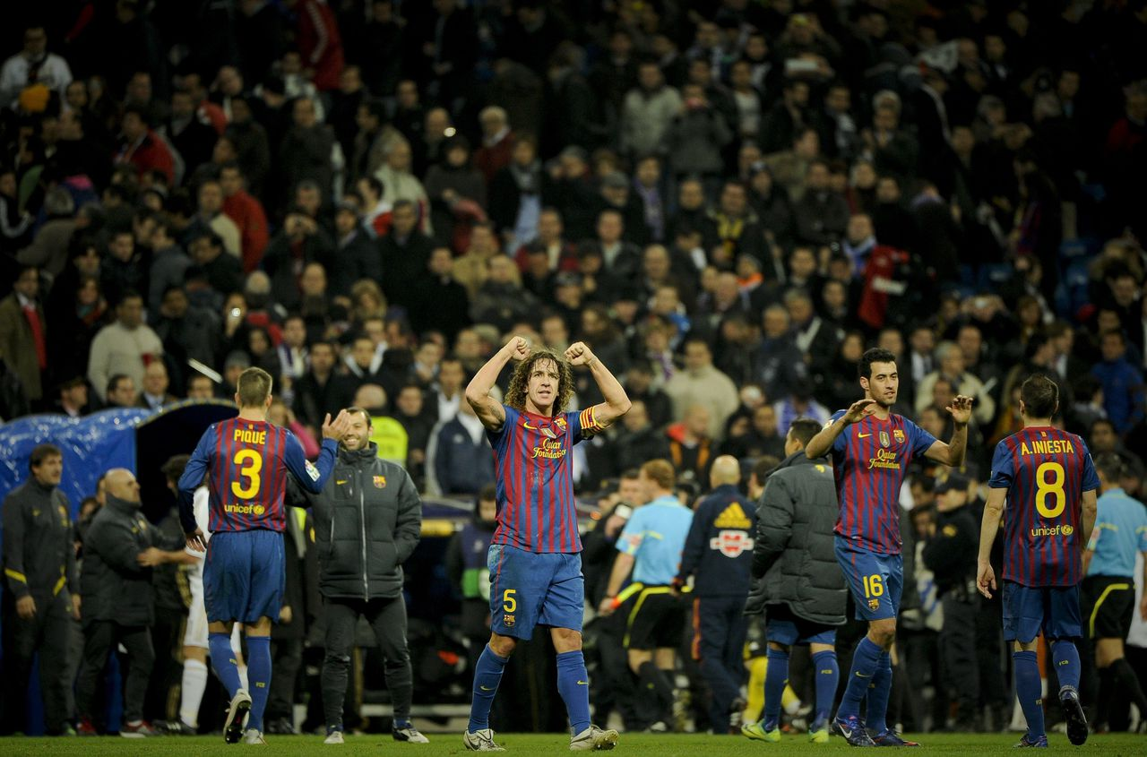 "Barcelona's captain Carles Puyol (C) celebrates after winning the Spanish Cup ""El clasico"" football match Real Madrid vs Barcelona at the Santiago Barnabeu stadium in Madrid on January 18, 2012. Barcelona won 1-2. AFP PHOTO/ PEDRO ARMESTRE"