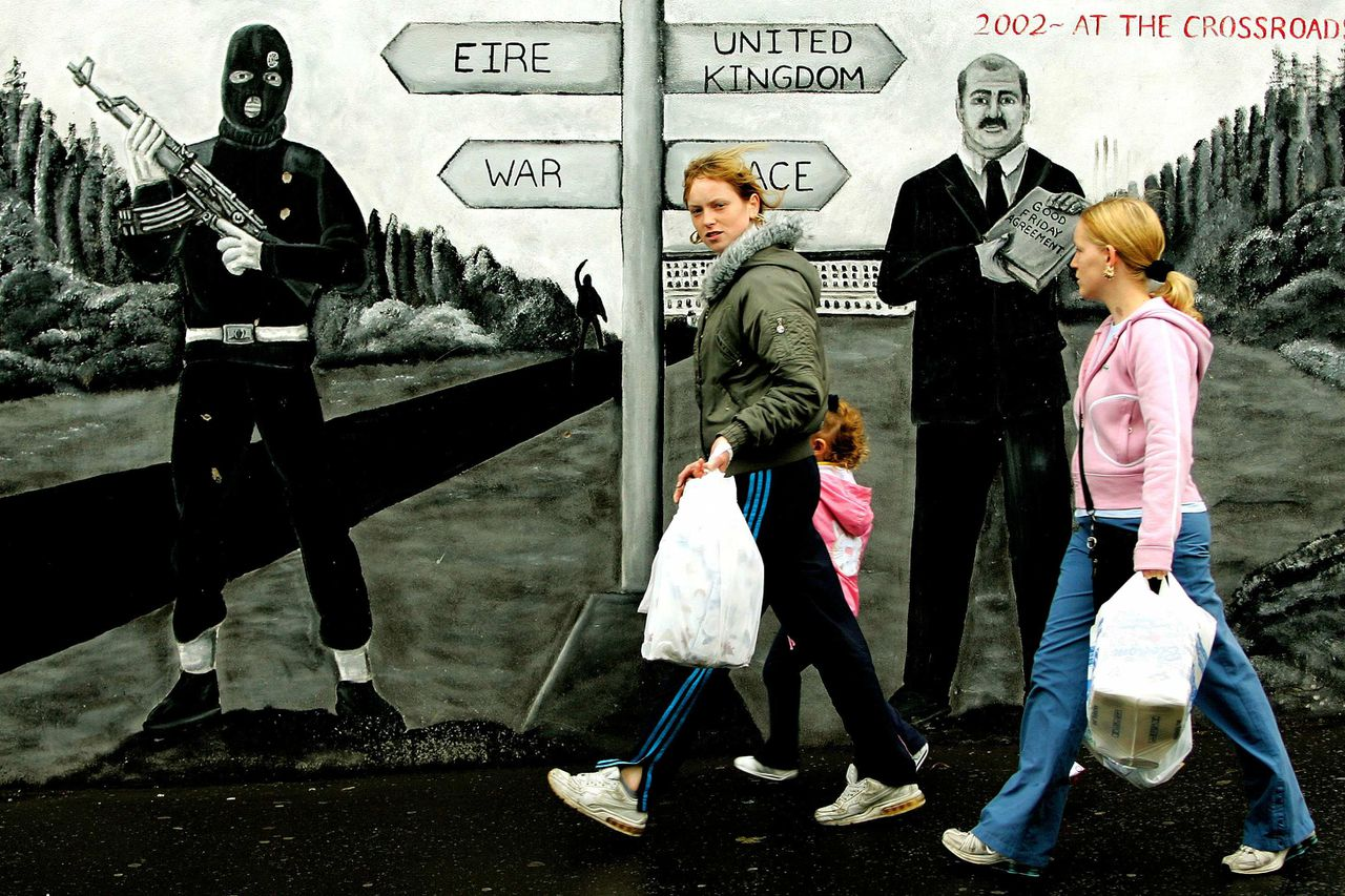Inwoners van Belfast lopen op de beruchte Shankill Road langs een muurschildering waarop het dilemma van de Noord-Ieren wordt uitgebeeld. (Foto Reuters) Members of the public walk past a mural depicting a fighter from loyalist paramilitary group, the Ulster Volunteer Force (UVF), on a street corner in Shankill Road in Belfast, northern Ireland, September 26, 2005. Irish nationalist guerrillas have given up the weapons that sustained their 30-year campaign, international monitors are expected to say on Monday. REUTERS/Dylan Martinez PICTURES OF THE YEAR 2005