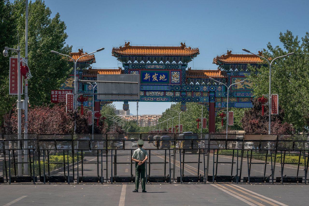Een politieman houdt de wacht bij de nu gesloten Xinfadi-markt in Beijing.