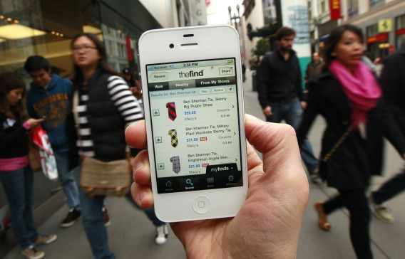 In this Nov. 23, 2011 photo, an Associated Press reporter demonstrates an app for shopping on her smartphone, in San Francisco. If you're trying to save cash and time this holiday season, a slew of smartphone apps can help.(AP Photo/Jeff Chiu)