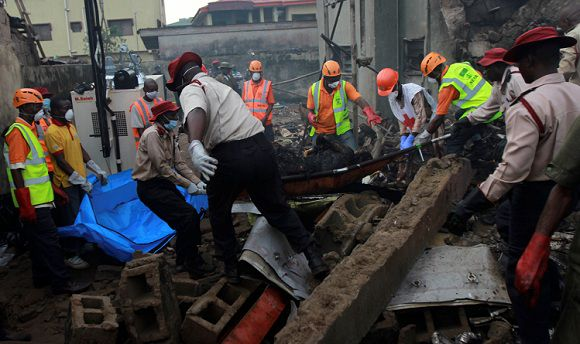 Name: 2012-06-04T183224Z_01_LAG18_RTRMDNP_3_NIGERIA-CRASH.JPG Caption: ATTENTION EDITORS - VISUAL COVERAGE OF SCENES OF INJURY OR DEATH Rescue workers remove a charred body on a stretcher from the site of a plane crash at Iju-Ishaga neighbourhood, Lagos June 4, 2012. Nigeria recovered bodies and searched for clues on Monday after an airliner crashed in a residential area of Lagos overnight, killing all 153 people on board and prompting the president to declare three days of mourning. REUTERS/Akintunde Akinleye (NIGERIA - Tags: DISASTER) TEMPLATE OUT IPTC Date: 18:32 04/06/12