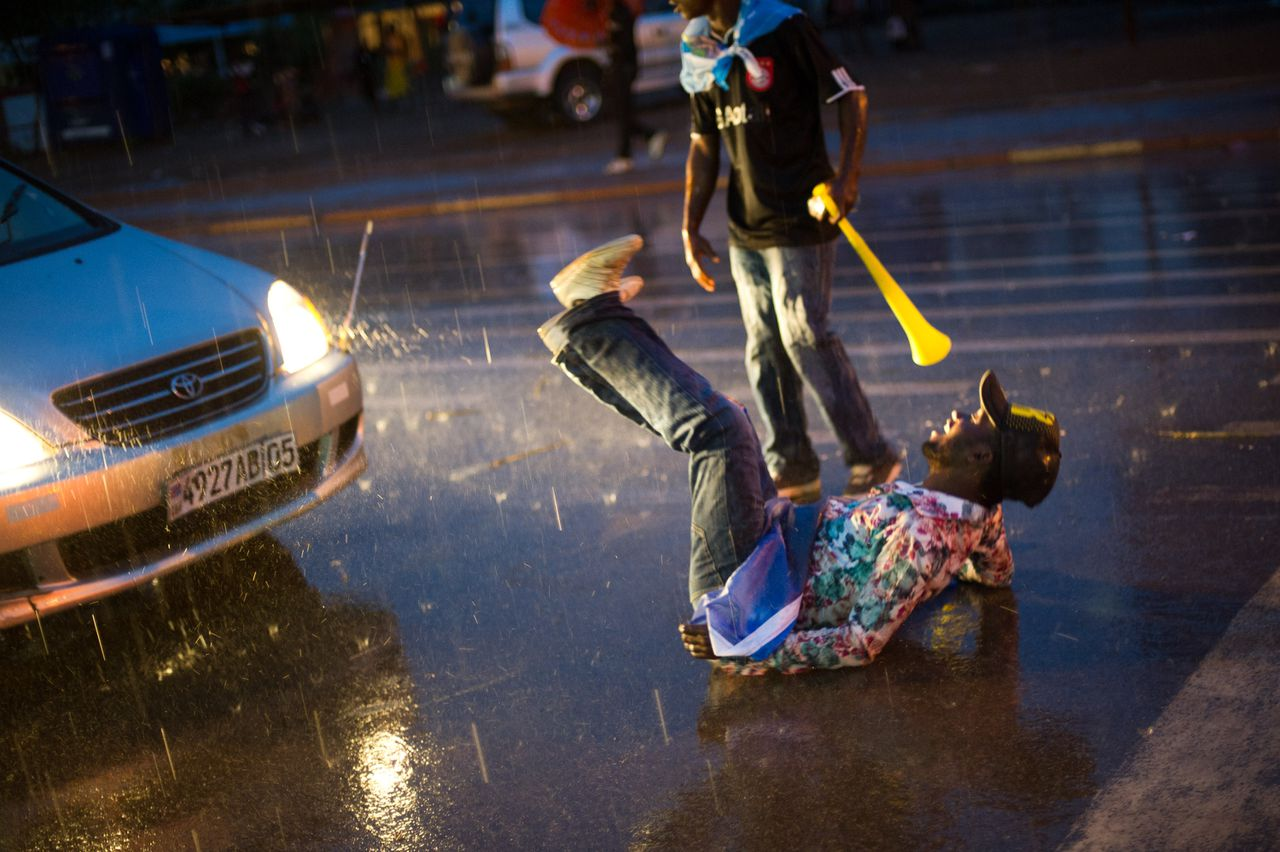 A man rolls on the street in front of a car as supporters of newly re-elected President Joseph Kabila celebrate in Lubumbashi's city centre on December 9, 2011, following the announcement of the provisional results of the presidential election in the Democratic Republic of the Congo. The Independent National Electoral Commission declared that Kabila won his native Katanga province with 89.97% of votes, winning the country's elections with 48.95% nationally. AFP PHOTO/ PHIL MOORE